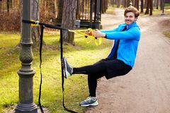 A man exercising with trx fitness strips. Attractive positive male exercising with trx fitness strips Royalty Free Stock Image