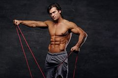 A man exercising with trx straps. A man working hard with fitness trx straps in a studio on grey background Stock Images