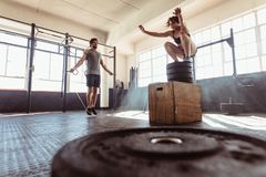 Athletic couple exercising hard at the gym. Man exercising using skipping rope and women jumping on box in gym. Athletic couple training hard at the cross fit Stock Image