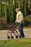Man Exercising with Walker. Elderly Friend with Parkinson Disease Exercising in Park with a Walker Stock Photography