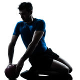 Man exercising workout fitness ball posture. One caucasian man exercising workout holding fitness ball posture in silhouette studio  isolated on white background Royalty Free Stock Photo