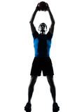 Man exercising workout holding fitness ball posture. One caucasian man exercising workout holding fitness ball posture in silhouette studio isolated on white stock image
