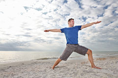Man exercising yoga at the beach. Stock Photo
