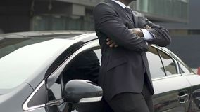 Man in expensive business suit wiping new car, happy with purchase of auto. Stock footage stock footage