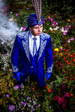 Man in expensive dark blue suit of illusionist pose on flower meadow. Stock Images