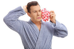 Man experiencing a toothache and holding an icepack. Young man experiencing a toothache and holding an icepack isolated on white background Stock Photography