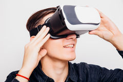 Man experiencing virtual reality through a VR headset isolated on white background. Young man experiencing virtual reality through a VR headset isolated on white Royalty Free Stock Photos