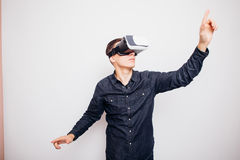 Man experiencing virtual reality through a VR headset pointed with hands isolated on white background. Young man experiencing virtual reality through a VR Stock Photo