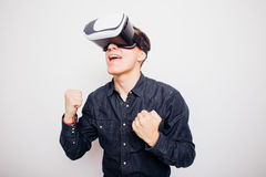 Man experiencing virtual reality through a VR headset. Young man experiencing virtual reality through a VR headset isolated on white background Stock Images