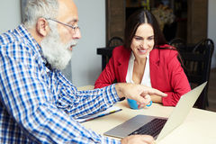 Man explaine something and woman looking at laptop Stock Photos