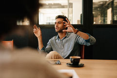 Man explaining business strategy to colleagues in conference roo Stock Image