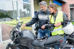Man explaining controls motorcycle to lady Royalty Free Stock Photo