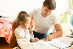 Man explaining daughter how to do homework Stock Photography