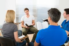 Man explaining gospel. Man Explaining To His Friends From Scripture Royalty Free Stock Images
