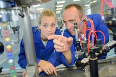 Man explaining machinery to female apprentice. Apprentice royalty free stock image