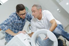 Man explaining problem with washing machine to technician. Washing royalty free stock photos