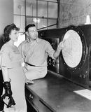 Man explaining about radar to a young woman in a control room Stock Image