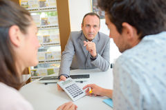 Man explaining something to clients on foreground Stock Image