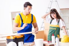 The man explaining woman woodworking tips in wood workshop. Man explaining women woodworking tips in wood workshop Stock Image