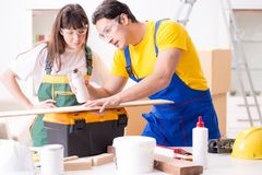 The man explaining woman woodworking tips in wood workshop. Man explaining women woodworking tips in wood workshop Stock Photos