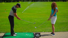 Man explains the girl how to play golf near course stock video footage