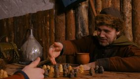 Man explains rules of popular strategy board game - tafl. Portrait of man in russian ethnic suit explains rules of medieval popular strategy board game - tafl stock video