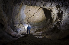 Man explorer in huge cave underground Stock Photography