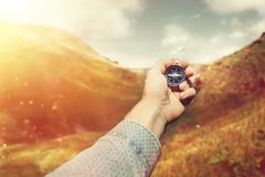 Man Explorer Searching Direction With Compass In Summer Mountains, Hand Point Of View Shot. Travel Journey Concept royalty free stock image