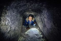 Man explores narrow passage in ancient abandoned underground chalky cave monastery Royalty Free Stock Photos