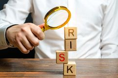 A man explores a tower of cubes with the word Risk. Search and correction of errors and failures. Risk management, cost assessment. And business and investment royalty free stock image