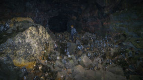 A man exploring a cave. A man standing in a sea of ice stalagmites in a lava tube tunnel in Iceland stock photo