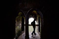 Man exploring dark castle. Man with backpack exploring dark medieval castle in Wales Royalty Free Stock Photography