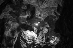Man exploring huge cave. Adventure travellers dressed cowboy hat and backpack, leather jacket. black and white, tourist route. royalty free stock image