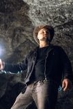 Man exploring huge cave. Adventure travellers dressed cowboy hat and backpack, leather jacket. extreme, tourist route. ancient royalty free stock image