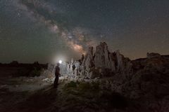 Man Light Painting Tufa near Mono Lake under the Milky Way Royalty Free Stock Photo