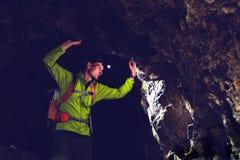 Man exploring underground dark cave tunnel. Man walking and exploring dark cave with light headlamp underground. Mysterious deep dark, explorer discovering Stock Images