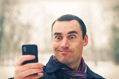 Man expresses emotion with mobile phone Royalty Free Stock Photo