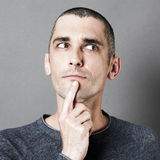 Man expressing doubt and reflection with finger on chin Royalty Free Stock Photos
