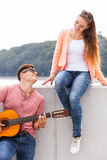 Man expressing his love by music. Romance dating sound talent valentines concept. Man expressing his love by music. Young girl listening to song played by Stock Images