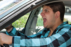 Man Expressing Road Rage. An irritated young man driving a vehicle is expressing his road rage Stock Images