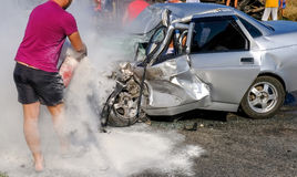 Man extinguishes the car with a fire extinguisher. Damaged vehic. Le closeup after car crash Stock Photography