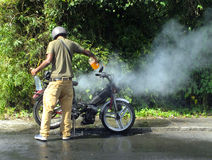 Man extinguishing fire. Road safety issue: man extinguishing fire from his motorcycle Royalty Free Stock Photography