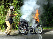 Man extinguishing fire. Road safety issue: man extinguishing fire from his motorcycle Royalty Free Stock Image