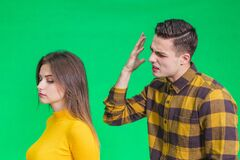 Man Extremely Angry At Girlfriend, Shouting At Her, Warnig With Fist, She Stands Back To Her, Not Paying Attention. Stock Photos