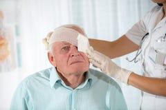 Man with eye bandage. Female doctor and senior man Royalty Free Stock Images