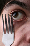 Man eye and fork Stock Image