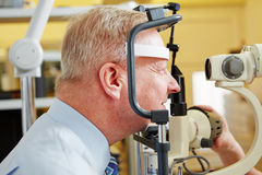 Man at eye measurement at. Senior men at eye measurement at ophthalmologist with slit lamp Royalty Free Stock Photos