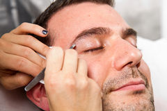 Man eyebrows with tweezers. Beautician plucking a beautiful man eyebrows with tweezers in a beauty salon royalty free stock photo