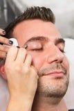 Man eyebrows with tweezers Royalty Free Stock Photos