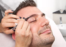 Man eyebrows with tweezers. Beautician plucking a beautiful man eyebrows with tweezers in a beauty salon Stock Image